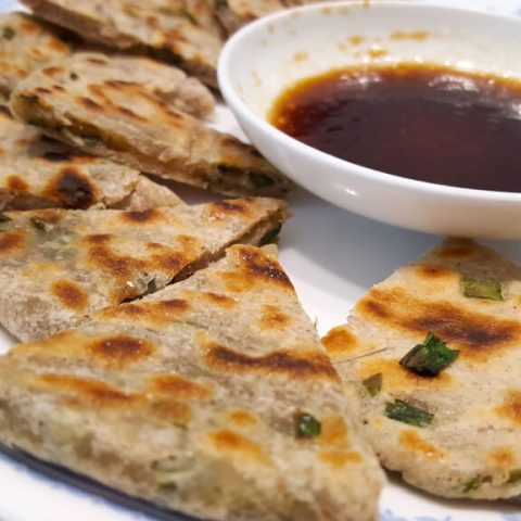 Chinese scallion pancakes cut up next to dipping sauce