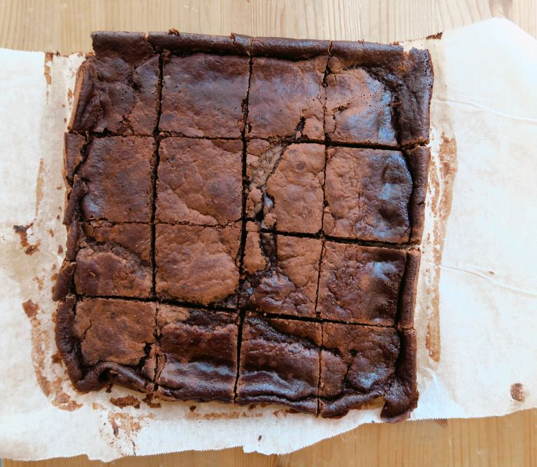 Heather's take on Boo's Ridiculous(ly low calorie) Brownie with a shiny, crinkled crust created using erythritol as a sweetener in place of sugar. Bird's eye shot on parchment paper on a wooden stool as backdrop :)